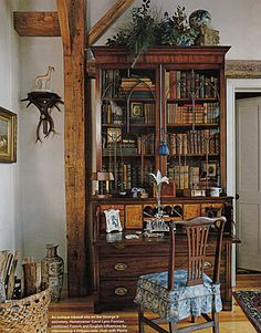 This majestic secretary is mostly filled with books, interspersed with a few decorative objects. It appears to be used for its original purpose as a desk. I like how the height is visually increased by having accessories on top too.