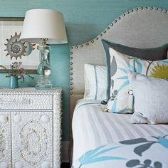 Beach Inspired    This bedroom uses hues of the sea, with a turquoise wallcovering and intricate shell-covered side table. The bedding plays nicely with the coastal shell picture framed on the wall.