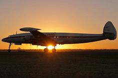 A C-121C Constellation sits with a sunset for a backdrop.