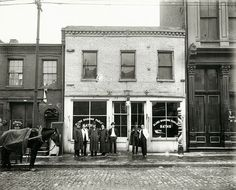 St. Louis Streets in the Early 20th Century. Group of men standing in front of the Globe Shaving Parlor at 1015 Carr. Photograph, ca. 1910.