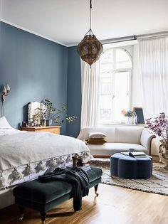 Decor feminino e eclético, com inspiração boho - um quarto super confortável, com parede azul e penteadeira charmosa. Vem ver no site.