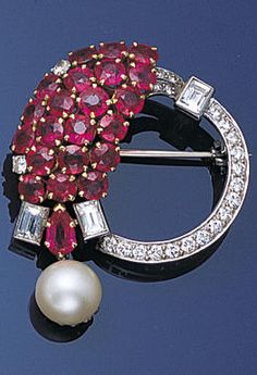 A ruby, diamond and cultured brooch, circa 1935, of hoop design set with brilliant and baguette-cut diamonds and a cascade of rubies suspending a single cultured pearl, the cultured pearl possibly a later replacement, length 4.1cm.
