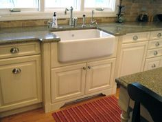 Kitchen.  Love the Apron Sink, the brick backsplash, and the faucet.  Do not like the white cabinets or countertop choices.