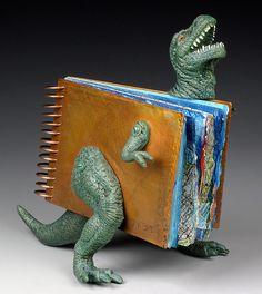 """Judith Hoffman: 7 Extinction Events ©2006, 7 x 7 x 3 inches. Cover: copper, etched in ferric chloride. Pages: Arches watercolor paper, collage, Golden acrylics. Plastic dinosaur with a book in his chest. I cut the dinosaur with a jeweler's saw and a mat knife, it's hollow inside. The front cover has an arm and a leg attached with nuts and bolts. From my gallery """"Artist's books with metal covers and paper pages"""" http://judithhoffman.net/gallery1/gallery1index.html"""