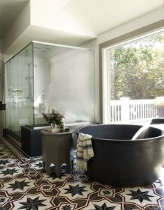Bobby Flay - Gorgeous bathroom with huge walk-in shower with seamless glass doors next to round black bathtub accented with gray Moroccan star tiled floor