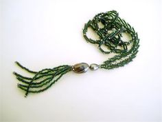 Green and silver long tassel necklace. Delicate beadwork band, edged in silver, with a single gray pearl and metallic bead topping a forest green beaded tassel. Seed bead necklace with a pearl tassel drop at center front.  Purple lined green seed beads make up the most of both band and tassel. These beads have a beautiful depth of color - vibrant forest green up front, with that extra special hint of something at the center. The edges of the band, and tips of each tassel strand, are capped…