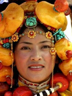 Tibet | Girl from Litang Horse Festival 2006 costume exhibition. Tremendous headpiece alone with huge amber and coral chunks must be at least 10 kilograms, whole costume could be 30 or more kilograms. | © BetterWorld2010