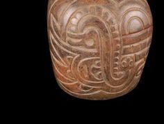 34/ CUPISNIQUE - côte Nord Pérou, -600/-200. Musée du Quai Branly. Vase en céramique noire tachée de rouge sombre et marron. Panse de forme grossièrement cylindrique. Fond plat. Sur le sommet de la panse, anse-goulot tubulée en étrier. Décor incisé. Serpent, ligne de festons, tête d'oiseau à long bec, tête humaine. Hauteur : 21 cm. Engobe rouge récurrent par la suite.