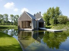 Designed by Belgian firm Wim Goes Architecture, this addition to an existing home floats above a man-made pond. Behind the open slats are glass panels that can be opened or closed
