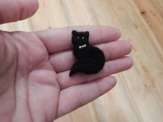 Needle felted black cat brooch.This felted cat brooch is made of 100% wool. Eyes and bow made of beads. This felted jewellery could adorn a bag, hat, scarf or coat; It will be an excellent present for a girl. It is about 2.5cm ( 1 inch) leinght and 3,5cm (1.4inch) in hight. There is a metal pin on the backside.   Actual color may be different from the colors in the photo, depending on your monitor settings  Jewelry will be shipped within 3-5 days after payment is received. Parcel will go for…