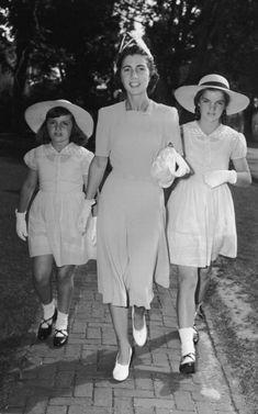 Jacqueline Bouvier, her mother, Mrs John V Bouvier III, and her sister, Lee, walk along a brick sidewalk while attending the Krech-Jackson wedding in East Hampton, Long Island,1941
