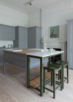 Plain English Design Spitalfields cupboards by Plain English with Folgate doors. Georgian Doors. Oak worktop to freestanding worktable. Island. Honed Carrara Marble worktops. Georgian cornice. Painted plain stools. Gloss paint. Plain English Pantry Cupboard. Tall Freestanding Cabinet. Overmantel Shelf. Oyster Stone Bateig Blue limestone worktops. Plain English Kitchen.