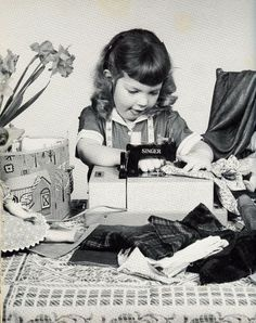 1960 Black and white photograph of little girl sewing on her old mini Singer sewing machine.