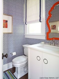 Laura Casey Interiors - bathrooms - Jonathan Adler Queen Anne Mirror, orange lacquered mirror, modern orange mirror, orange queen anne mirror, contemporary white vanity, nickel ring pull hardware, white counter, rectangular porcelain sink, chrome faucet, navy geometric wallpaper, navy fretwork wallpaper, wallpapered powder room, orange abstract art print, blue and green striped rug, window trim, navy grosgrain trimmed roman shade, navy and white roman shade, navy and white wallpaper, modern…