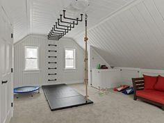 To create a fun and liveable space for kids to play and guests to visit, these knotty pine walls and ceiling were painted white, a new carpet was installed and gas pipe was purchased at a local plumbing supply warehouse, painted black and then installed as a ladder and monkey bars. A gym grade climbing rope was also installed as another way to get down from the monkey bars. Builder: Reap Construction vermontcontractor.com Photo: Susan Teare susanteare.com