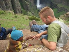 peacecorps guy is showing a child his skin. Many children around the world have not seen caucasian skin and are fascinated