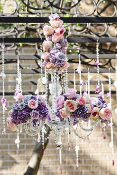 Freaking amazing crystal chandelier covered in purple & pink roses. - BZ Events
