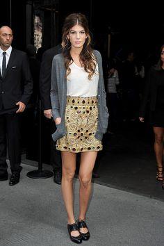 Bianca Brandolini. Gold Dolce&Gabbana skirt, white top, grey cardigan and black flats