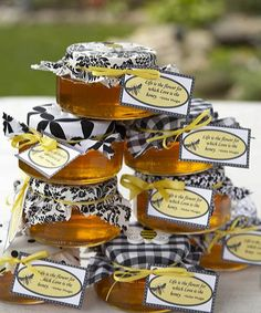 Sweet jars from a local honey farm served as party favors for wedding guests. Smith matched them to the wedding décor by covering them with swatches of different black and white fabrics. Wooden bumblebees and yellow ribbons bearing a romantic poem by Victor Hugo completed the homespun favors.   - CountryLiving.com