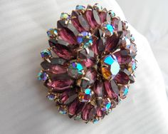 Vintage Aurora Borealis Rhinestone Brooch 1950s  Beautiful piece in excellent condition, Two inch circular pin has Sparkling Lavender Tear Drop Baggetts surrounded by Rainbow Aurora Borealis Stones, All prong Set Stones. Larger Aurora Borealis in Center, includes 27 Aurora Borealis and 27 Lavender Baggetts, Finished with a rollover clasp. Amazing Piece for a Mothers Day Gift.  Condition-Clasp is slightly bent, slight bit of patina on clasp.  Measures-2X2 inches  Please check out my other…
