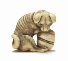 A Japanese ivory netsuke of a puppy and a ball Edo, 18th Century, signed Okatomo Carved in seated position, one paw resting on the ball