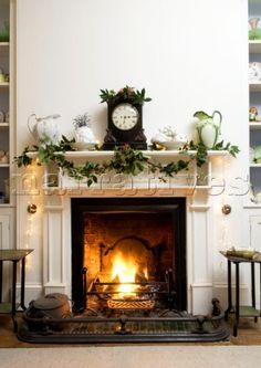 Open fire burning in grate with festive decorations on the mantlepiece