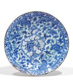GRAND PLAT SAFAVIDE DU XVIIe SIÈCLE  en céramique à décor de fleurs bleues sur fond blanc et blanches sur fond bleu cerné de blanc. Bordure florale, sous glaçure céladon transparente craquelée. Dos sous une épaisse glaçure verdâtre.(Cassé-collé complet sur l'aile 14 x 3 cm, fêlure et égrenures).  Iran, Kirman, début du 17e siècle.  Diam. 44 cm