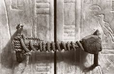 Photograph by Harry Burton,  Griffith Institute, Oxford  1923, previously unpublished in NGM    Still intact in 1923 after 32 centuries, rope secures the doors to the second of four nested shrines in Tutankhamun's burial chamber. The necropolis seal—depicting captives on their knees and Anubis, the jackal god of the dead—remains unbroken, a sign that Tut's mummy lies undisturbed inside.