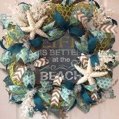 """""""Life Is Better at the Beach Wreath""""($126) There is a uniqueness to this square wreath...it definitely stands alone. It will make a statement on your beach house!!! It is 28""""x28""""x8"""" deep, on a white wire frame, burlap deco mesh, decorative lime wire web, beaded starfish, white seashore foliage, wood signage, 2.5"""" grey/aqua print ribbon, 2.5"""" multi color chevron ribbon, 1.5"""" blue ribbon, 1.5"""" burlap/white chevron ribbon. If interested, please message me. Thank you!"""