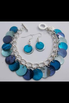Blue Shell Button Charm Bracelet with Matching Fish Hook Earrings. Handcrafted using a silver plated chain. Measures 7 1/2 inches and fastens with a toggle and clasp. £7.00