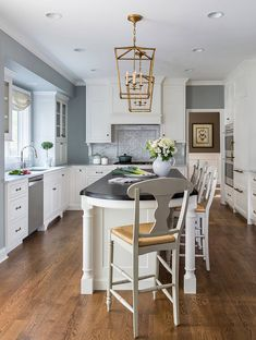 Traditional white kitchen with cabinets painted in Benjamin Moore Simply White, an island with bookshelves, marble backsplash and a custom hood Eclectic Kitchen, Rustic Kitchen, Kitchen Decor, Kitchen Design, Kitchen Ideas, Kitchen Paint, Kitchen Backsplash, Small Kitchen Table Sets, Small Space Kitchen