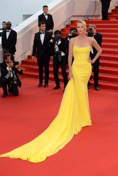 Charlize Theron eligió para la presentación un espectacular vestido con cola de Dior en tono amarillo y joyas de Chopard.