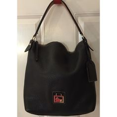 """DOONEY & BOURKE BLACK HANDBAG MED. NORTH/SOUTH SAC GENTLY USED DOONEY & BOURKE BLACK HANDBAG. THE STYLE IS MEDIUM NORTH/SOUTH SAC. COMES WITH A CUTE LUGGAGE TAG.  IN VERY GOOD CONDITION WITH SOME MARKS AND OR SMALL STAINS ON THE INSIDE.  COMES WITH THE ORIGINAL TAGS. GREAT TO CARRY FOR WORK OR PLEASURE. NO NEED TO SWITCH BAGS. APPROX 13"""" TALL 13 1/2"""" WIDE. OVER ALL A GREAT BAG!!! Dooney & Bourke Bags Shoulder Bags"""