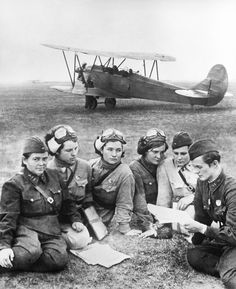 "worldwar-two: "" Squadron commanders of the Soviet 588th Night Bomber Regiment - the Night Witches - plan a combat mission, a Polikarpov Po-2, their main aircraft, visible in the background, 1942...."