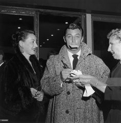 1950s: Actor Robert Mitchum (1917 - 1997) stops to sign an autograph for a woman while exiting a nightcub with his wife Dorothy, Hollywood, California.