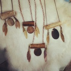 Long chain deer antler necklace with smooshed pennies and metal feathers.