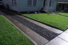 Crushed Black Granite In The Drive Way In The Front Yard With Green Grass With Black Stone Border With Stone Pavers and Walkway