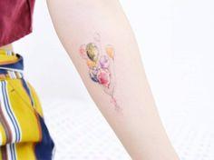Watercolor balloons on the left inner forearm. Tattoo artist:...