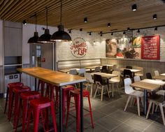 The new look of KFC! Love: The industrial elements - exposed brick walls (wallpaper), metal stools and light fixtures. Love the pop of colour of red stools.