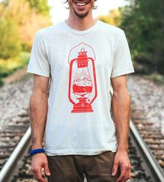 Guiding outdoorsy types to adventure, the camping lantern on this t-shirt reveals a mountain range and the rising sun straight ahead. The illustrated camping design is screenprinted by hand with soft water-based ink on an even softer tri-blend t-shirt, so comfy it might become a serious contender for your favorite tee.