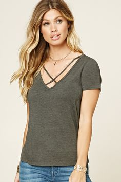 A heathered knit top featuring a V-neckline with crisscross straps, short sleeves, and a boxy silhouette.