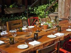 Mismatched garden chairs provide an ad hoc look. Table centerpieces vary, but always include greenery (of course).