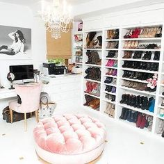 The Coveteur - Ashley Tisdale - Incredible closet with white walls, white floors with gold inlay detail and velvet pink tufted ottoman and pink velvet chair. Wall to wall shoe storage, crystal chandelier and black and white photography