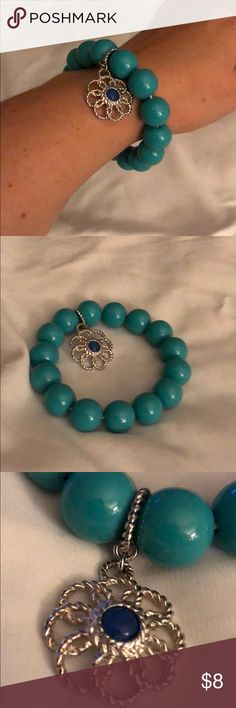 Teal Elastic Bead Bangle Teal bead bracelet with a silver hanging flower charm with a sapphire center. It's stretchy on elastic fits one size and plus size wrists. Jewelry Bracelets