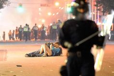 Stop for a kiss ...  this picture of a couple cosying up while a riot goes on around them in Vancouver has gone viral on the internet.