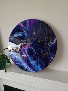 Unique red and blue hand made resin flow art oval ornament on a metal display white