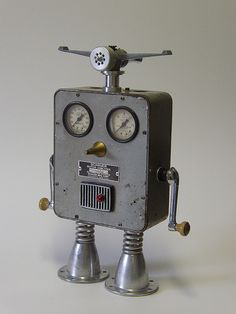 """Schauer robot    Schauer (15"""")  Wide-eyed and up for a challenge nothing gets past Schauer. Gloriously displaying his radar headgear (lawn sprinkler) and dual window cranks (arms) this bot is master of all he surveys. A vintage motor analyzer case, auto valve bodies, electric drill parts, springs  and a big gold nose keep him on top of his game."""