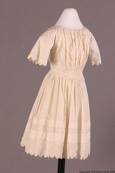 Girl's white cotton dress, American, 1840-50. Self-fabric piping at neck, waist and sleeves. White embroidery at hem; hem and cuffs finished with irregular scalloping and crochet trim. This young girl's dress was used for parties and other special occasions, and was probably worn during the summer, possibly under other clothing. The styling mimics adult women's fashions of the time.
