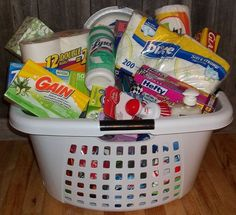 A laundry basket filled to the brim with Windex, Febreeze, toilet bowl cleaner, laundry detergent, napkins, etc. for bridal shower, wedding presents or new home owner.