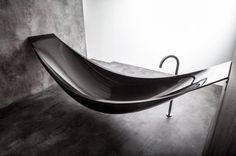 True hammock style carbon fiber bathtub. Suspended from the walls, this 8.8' bathtub doesn't even have a drain pipe. A drain is installed in the floor below it so when you pop the stopper the water falls to the floor and into the drain.